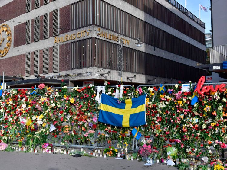 Flowers, candles and a Swedish national flag have been placed at a barrier in front of the Ahlens department store