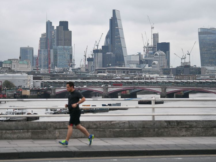 A jogger runs across a bridge spanning the River Thames as skyscrapers in the City of London are pictured om the horizon in London on March 29, 2017