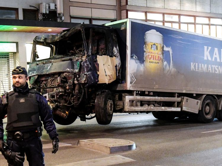 A truck tows away the hijacked lorry which struck pedestrians and crashed into a department store