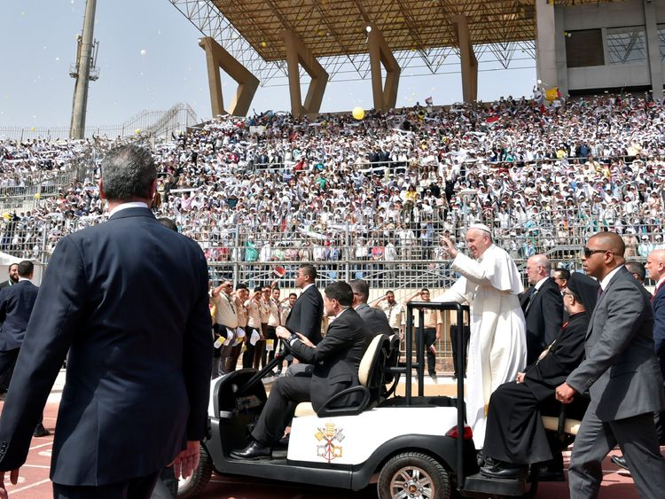 Pope Francis waves as he arrives to lead a mass in Cairo