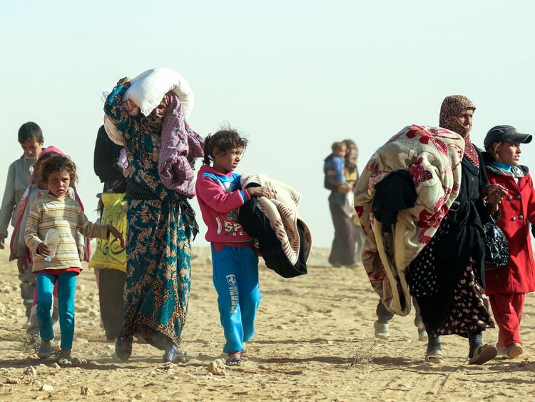 Syrian women and children travel from areas controlled by jihadists of the Islamic State (IS) group, en route to safety in areas held by by Kurdish-Arab Syrian Democratic Forces (SDF) alliance, on November 9, 2016, near the village of Mazraat Khaled, some 40 km away from the Islamic State group's (IS) de-facto capital of Raqa