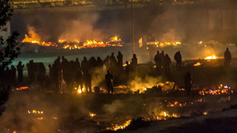 Migrants are evacuated as a huge fire blazes through the Grande-Synthe migrant camp outside the northern French city of Dunkirk