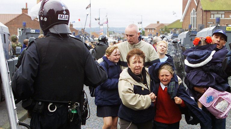 Children and parents run for cover amidst heavy police security, after a suspected blast bomb was thrown as they were making their way along the Ardoyne Road in north Belfast, towards Holy Cross School. The attack came on the third day of sectarian clashes in 2001
