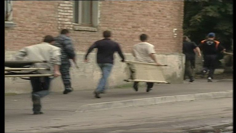 People run with stretchers during the Beslan school massacre