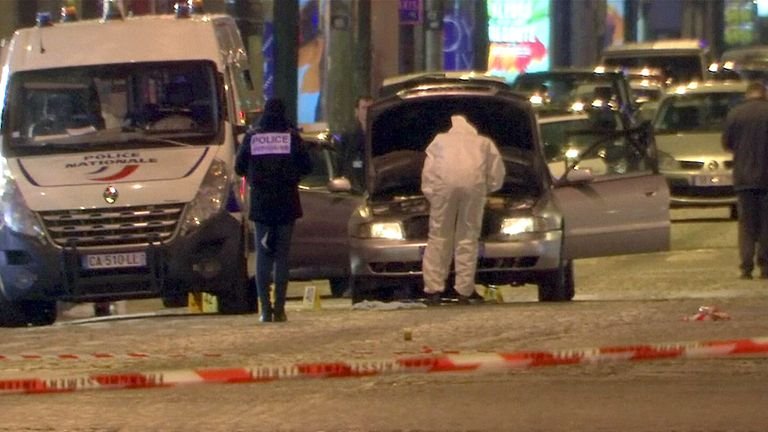 Police forensic investigators inspecting the car used by the attacker on the Champs-Elysees