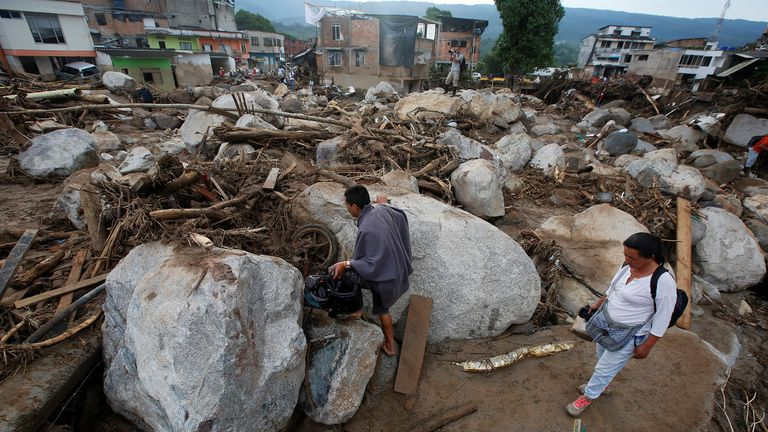People walk on a street destroyed after flooding and mudslides, caused by heavy rains leading several rivers to overflow, pushing sediment and rocks into buildings and roads, in Mocoa, Colombia April 2, 2017