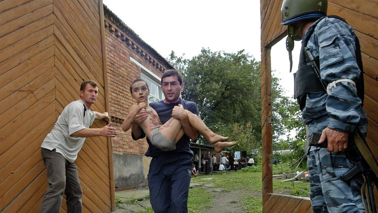 A man carries an injured boy during the rescue operation in the town of Beslan, North Ossetia