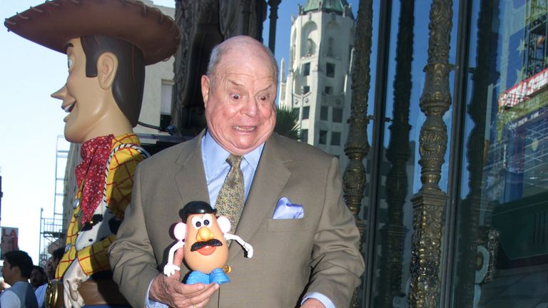 Comedian Don Rickles holds a Mr. Potato Head toy as he poses standing on top of his Hollywood star
