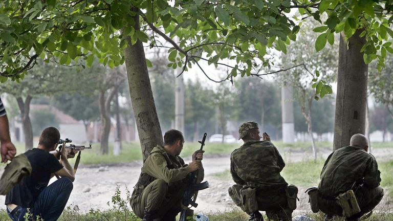 Ossetian soldiers take position near the school