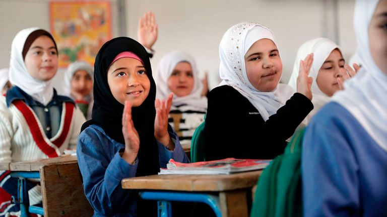 Syrian girls gesture during a visit to the Zaatari refugee camp, which shelters some 80,000 Syrian refugees on the Jordanian border with war-ravaged Syria, by United Nations Secretary General on March 28, 2017