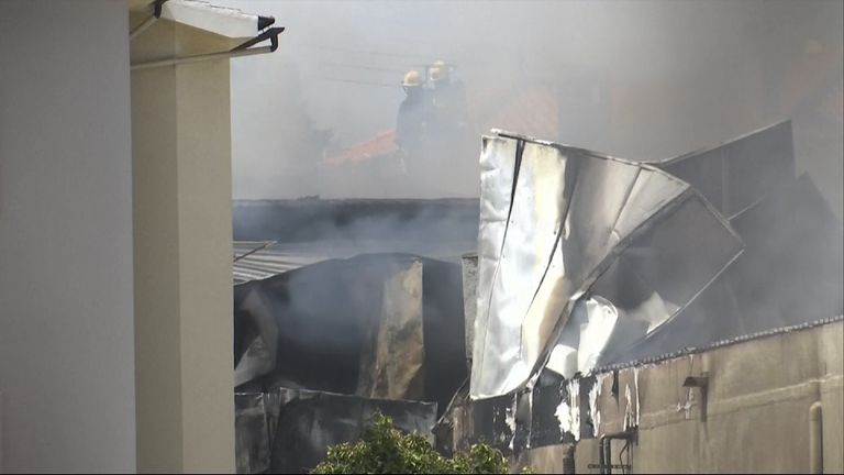 Firefighters can be seen through the smoke surrounded by metal from the building