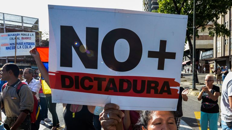 The sign held up by a protester during an anti-government march reads 'No more dictatorship'