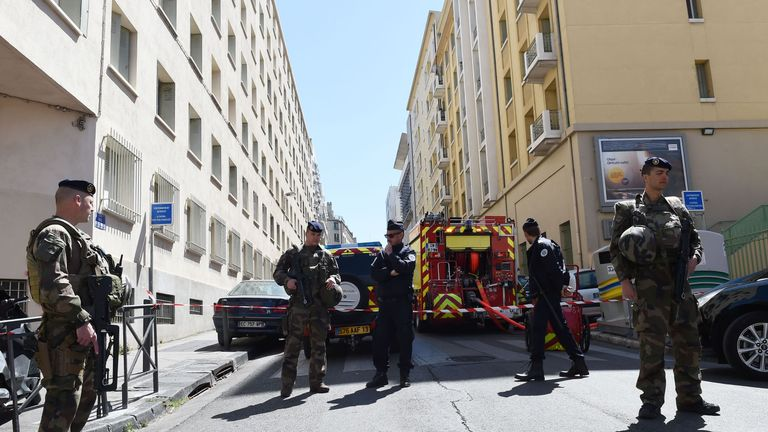 French soldiers, policemen and firefighter vehicles at the site of a police search