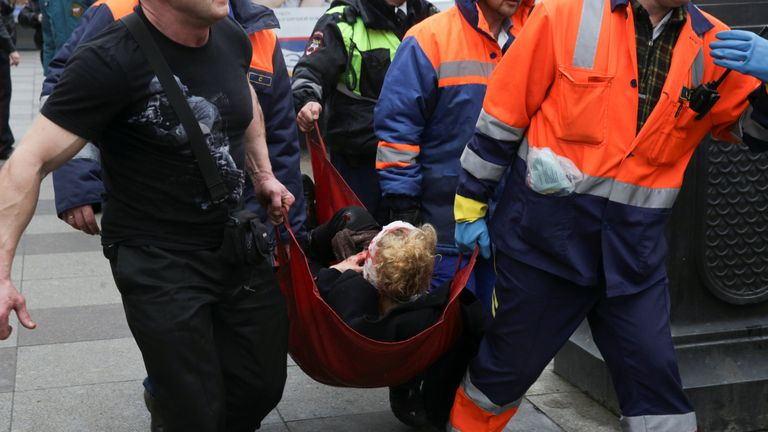 An injured person is helped by emergency services outside Sennaya Ploshchad metro station following explosions in St. Petersburg