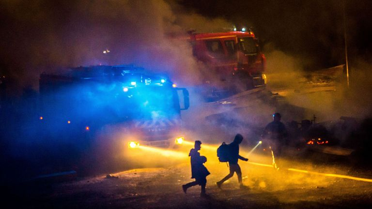 Migrants are evacuated after a huge fire at the Grande-Synthe migrant camp outside the northern French city of Dunkirk