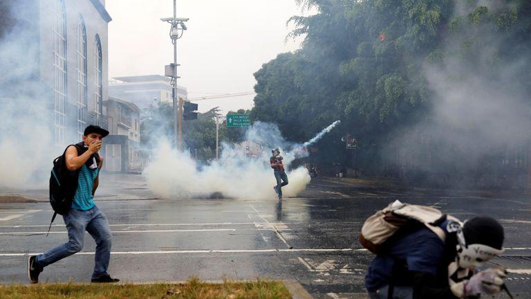 Demonstrators clash with riot police while rallying against Venezuela's President Nicolas Maduro in Caracas, Venezuela