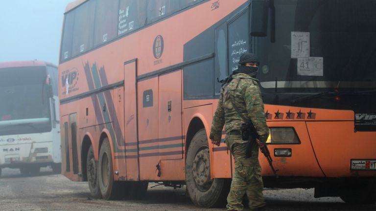A rebel fighter stands near busses carrying evacuees from two villages