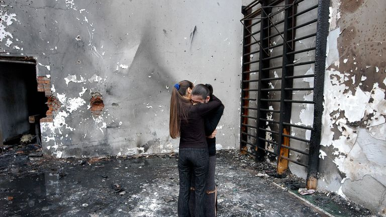 Two girls hug while they stand in the destroyed school gym in Beslan