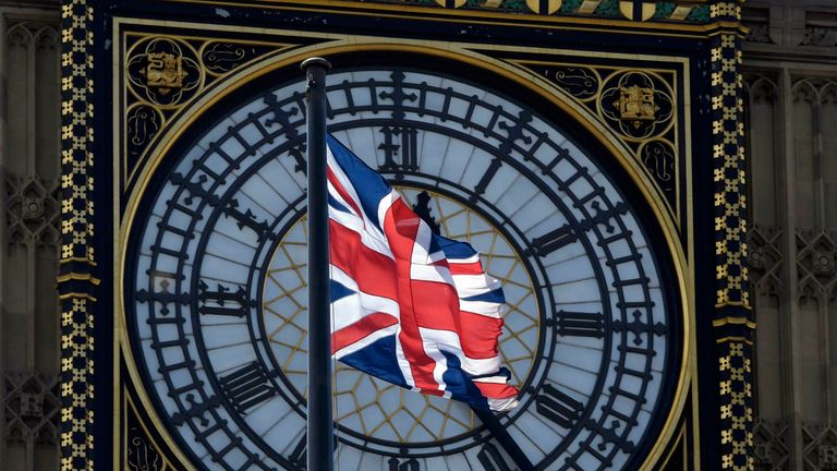 A Union Flag flies in front of the Big Ben clock face abover the Houses of Parliament