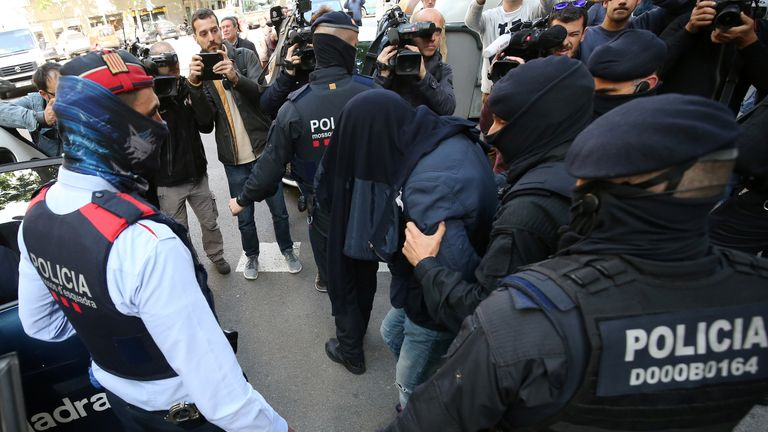 Spanish police lead a suspect toward a police car during a sweeping operation at some 12 locations against suspected Islamist militants
