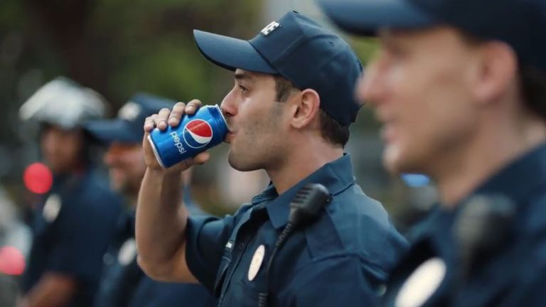 The crowd is heard cheering as a police officer drinks a can of Pepsi