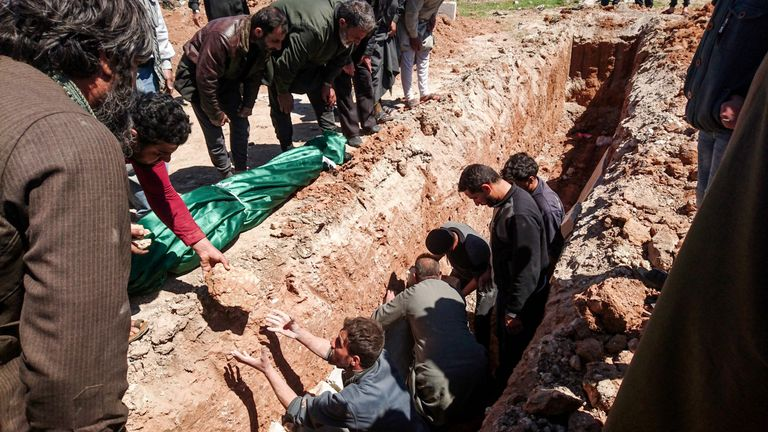 Syrians dig a grave to bury the bodies of victims of the suspected toxic gas attack