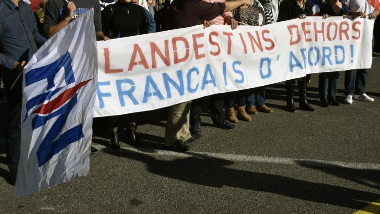 Front National supporters wave a banner reading 'Illigal immigrants out, French citizens first'
