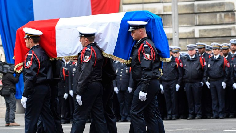 Officers carry Xavier Jugele's coffin during the ceremony