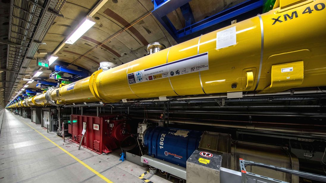 View into the 2.1-kilometre long accelerator tunnel of European XFEL with the yellow superconducting accelerator modules hanging from the ceiling (photo: DESY/D. Nölle)