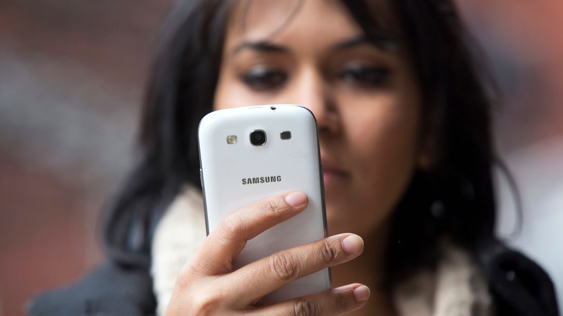 A woman uses a mobile phone in north London February 20, 2013