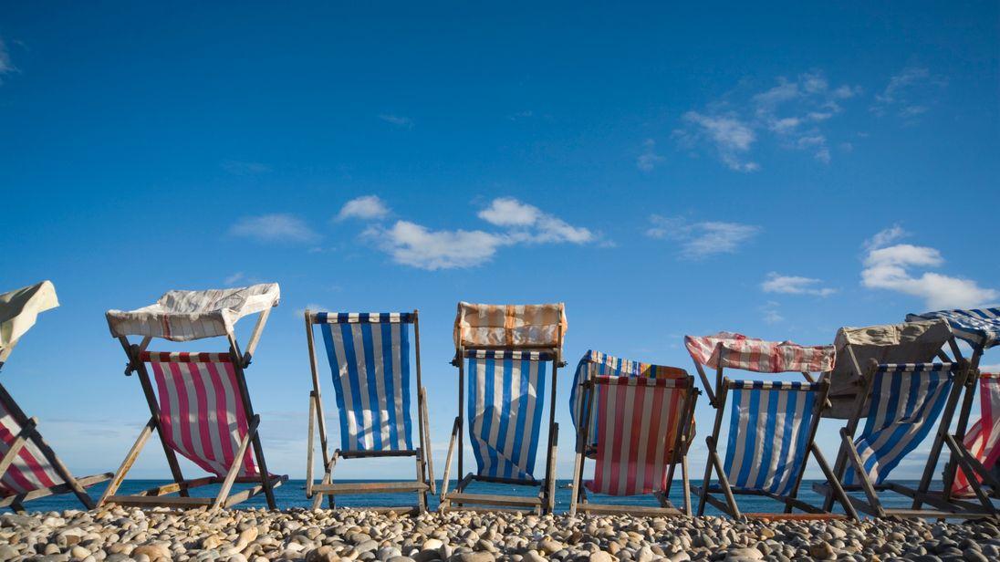Deckchairs line up along the beach.