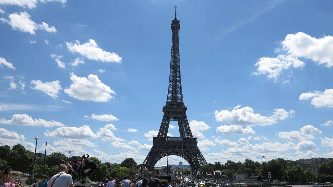People enjoy a sunny day next to the Trocadero fountains, in front of the Eiffel Tower
