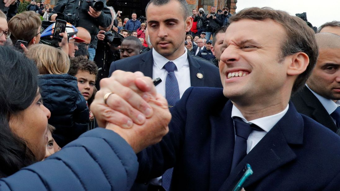 Emmanuel Macron greets supporters as leaves a polling station in Le Touquet