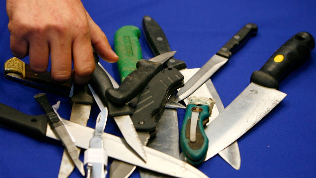 A Metropolitan Police representative arranges knives, seized in recent operations, for photographers after a news conference about knife crime, at New Scotland Yard, in central London on May 29, 2008