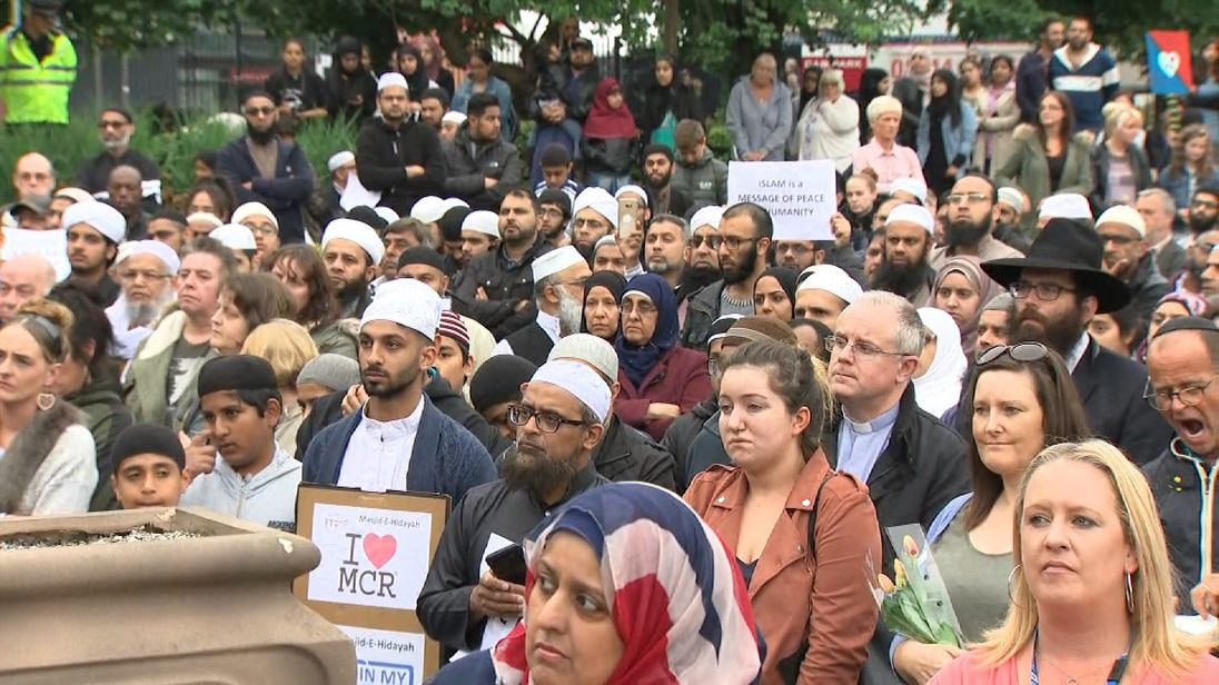 People listen as Trafford Youth Trust Director Dan Kupusarevic addresses them at a vigil for terror victims in Manchester