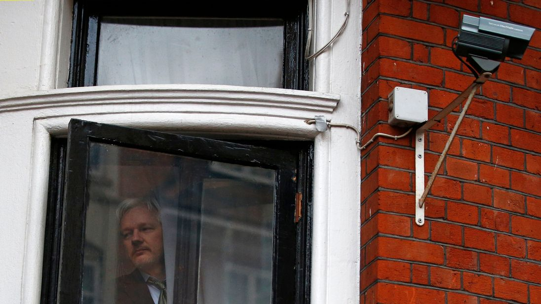 Julian Assange looks outside the window of the Ecuadorian embassy