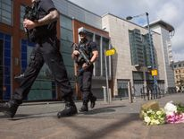 Police walk past the first floral tributes to victims of the attack