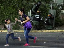 A woman and a girl run away as riot security forces and demonstrators clash during a protest against Venezuela's President Nicolas Maduro's government in Tariba, Venezuela