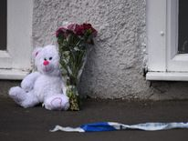 A floral tribute and a teddy bear are left by police tape near the venue