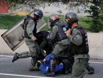 An opposition supporter is detained by riot police during a rally against President Nicolas Maduro in Caracas