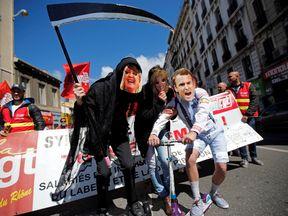 Protesters wearing masks depicting Emmanuel Macron and Marine Le Pen in Paris