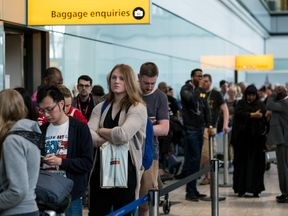 People queue to speak to British Airways representatives at Heathrow Airport Terminal 5
