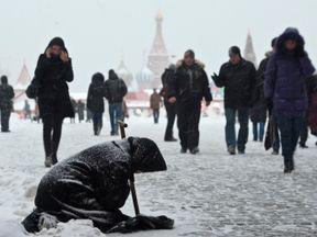 A woman begs for money during heavy snowfall in central Moscow, December 21, 2010