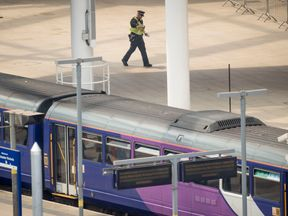 A police officer patrols Manchester Victoria during its closure after the terror attack