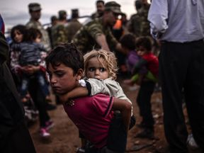 Syrian children displaced by the civil war cross the border to Turkey