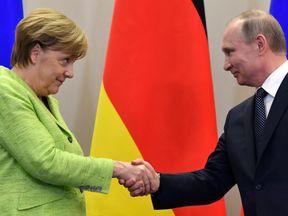 Vladimir Putin and Angela Merkel shake hands during their talks in Sochi