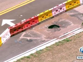 The sinkhole in the road next to the estate. Pic: NBC News