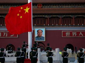 Chinese paramilitary policemen perform a flag lowering ceremony in Tiananmen Square