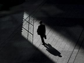 A man walks on a street between buildings at a business district in Tokyo, Japan, November 19, 2015