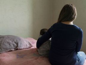 A mother and her child pose in a room in a temporary apartment of the Home association in Paris on November 22, 2016